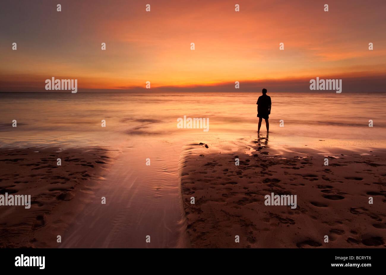 Silueta de un hombre de pie a la orilla del mar viendo la puesta de sol. Playa de estalactitas, Darwin, Territorio Imagen De Stock