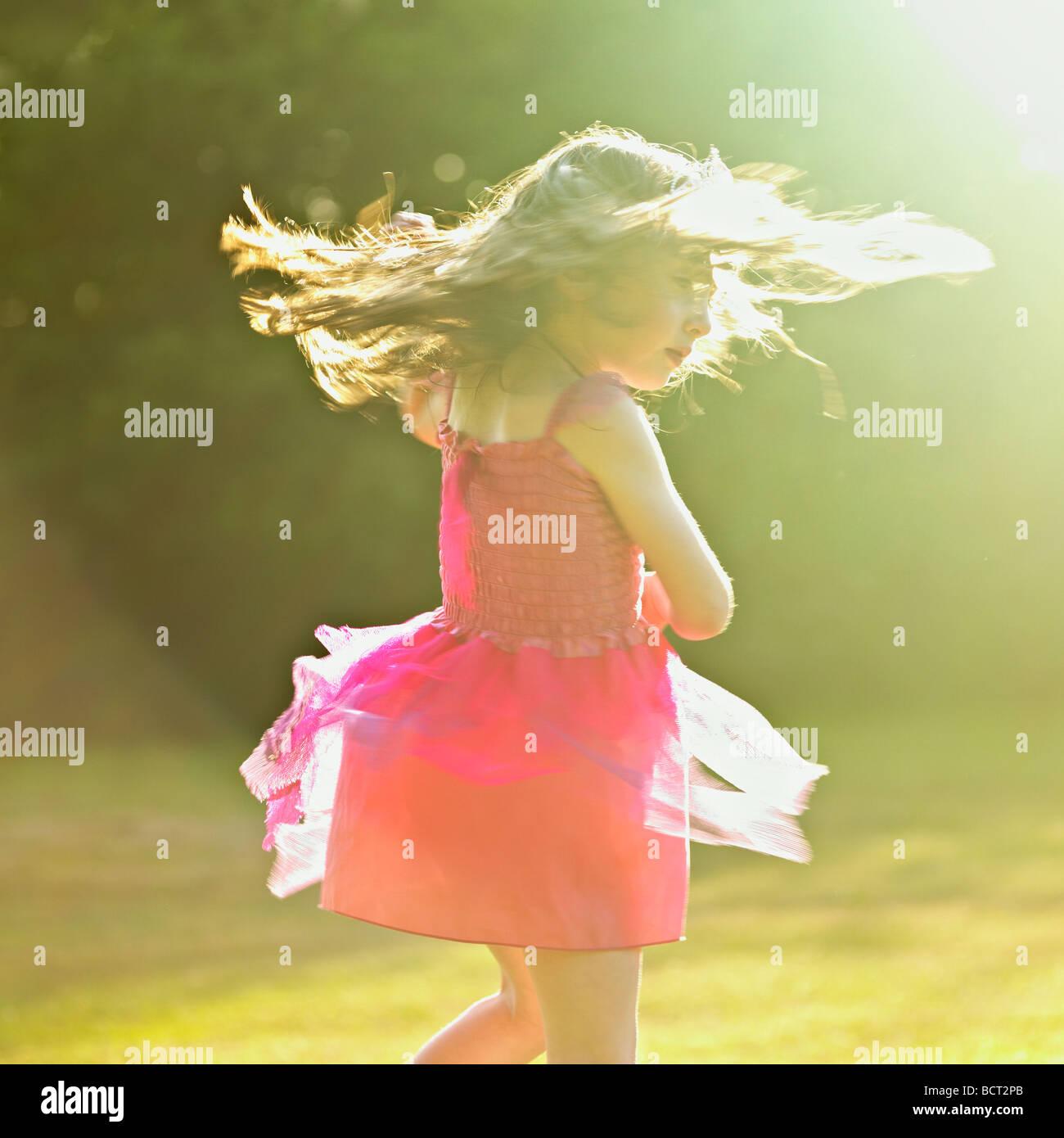 Niña en un vestido rosado bailando en el jardín sol de verano. Foto de stock