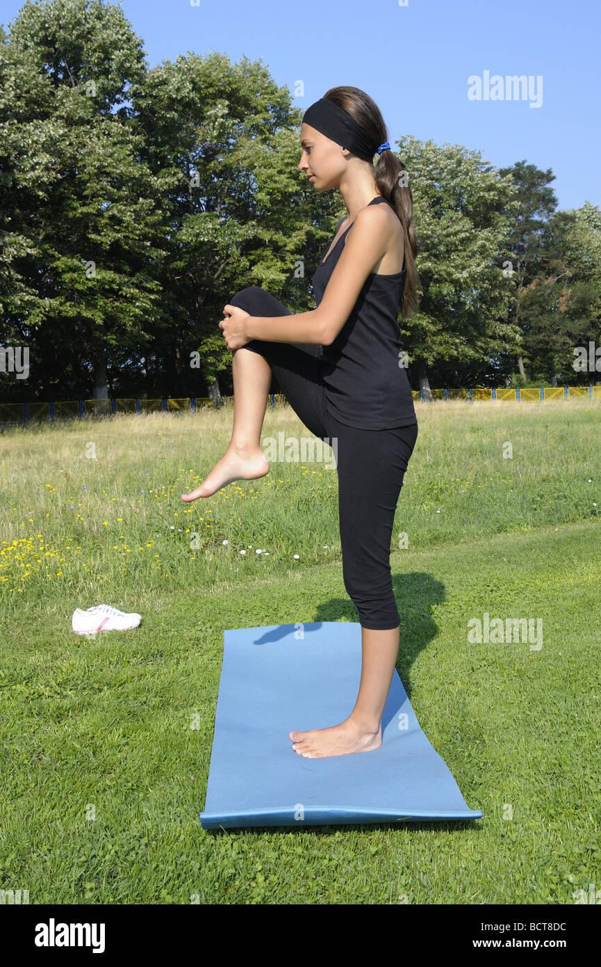 a6b304135 Chica haciendo ejercicio de estiramiento para la parte superior del tendón  de la corva, caderas y nalgas