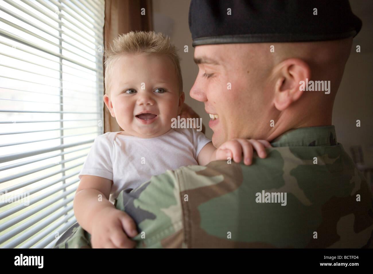 Padre militar estadounidense Coming Home y saludando a su hijo con un abrazo Imagen De Stock