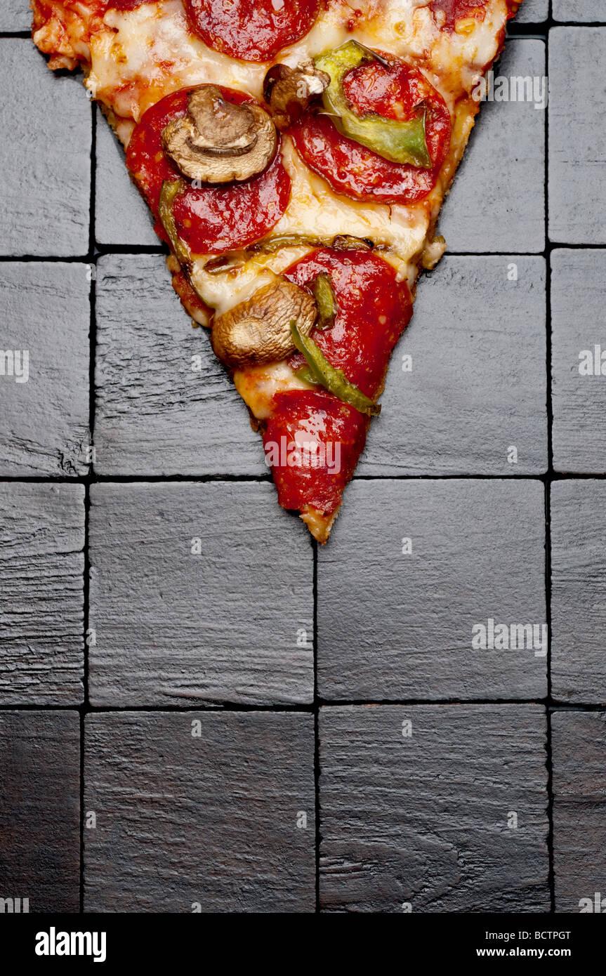 Una porción de pizza sobre un fondo de madera negra Imagen De Stock