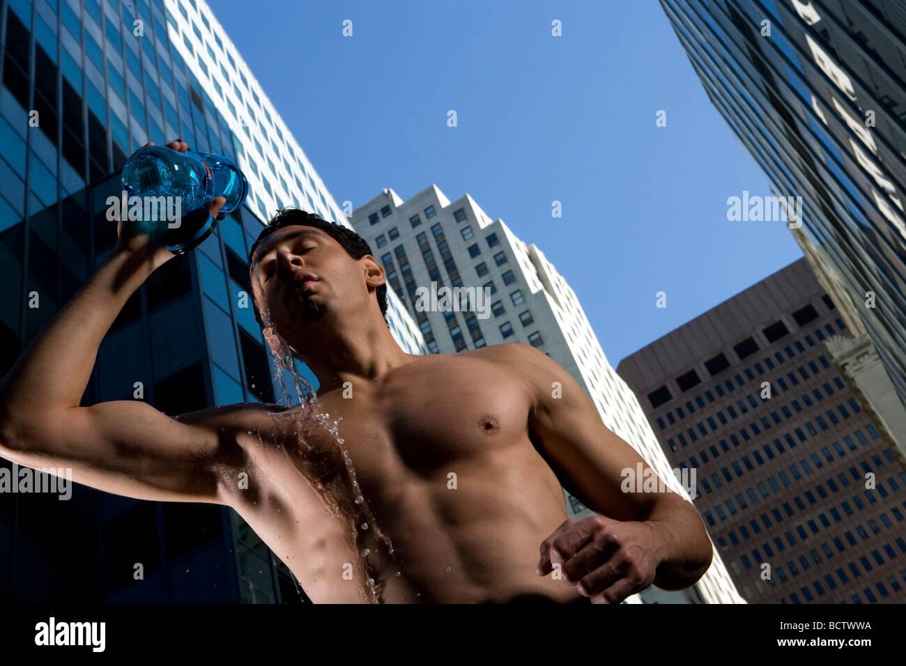 Ángulo de visión baja de un joven de verter agua sobre su cara con rascacielos en el fondo Imagen De Stock