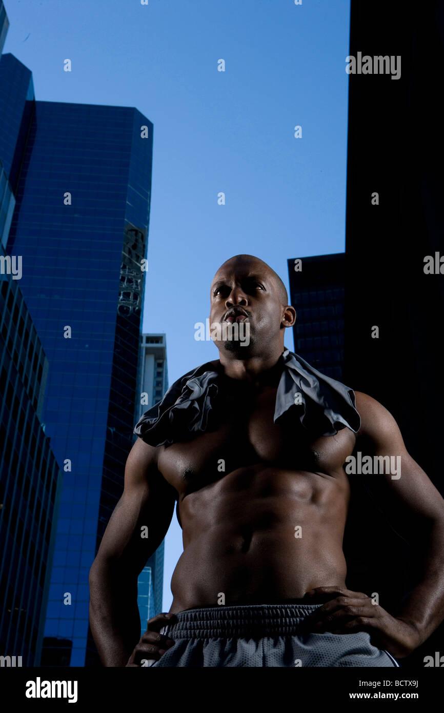 Ángulo de visión baja de un hombre adulto medio resoplando sus mejillas con los brazos sueltos Imagen De Stock