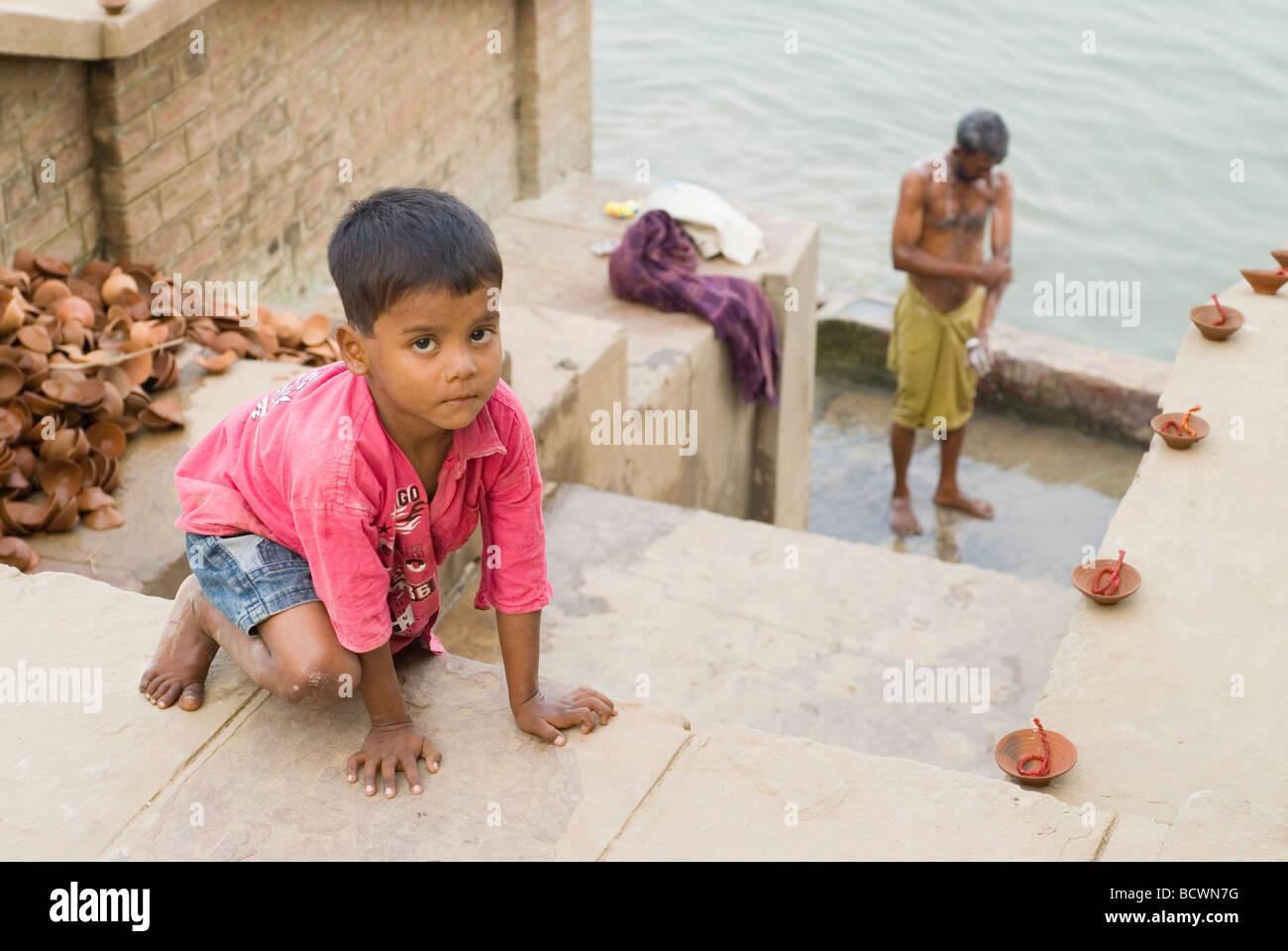 Un niño pequeño y un hombre durante la preparación para el festival de Diwali. Varanasi, India. Imagen De Stock