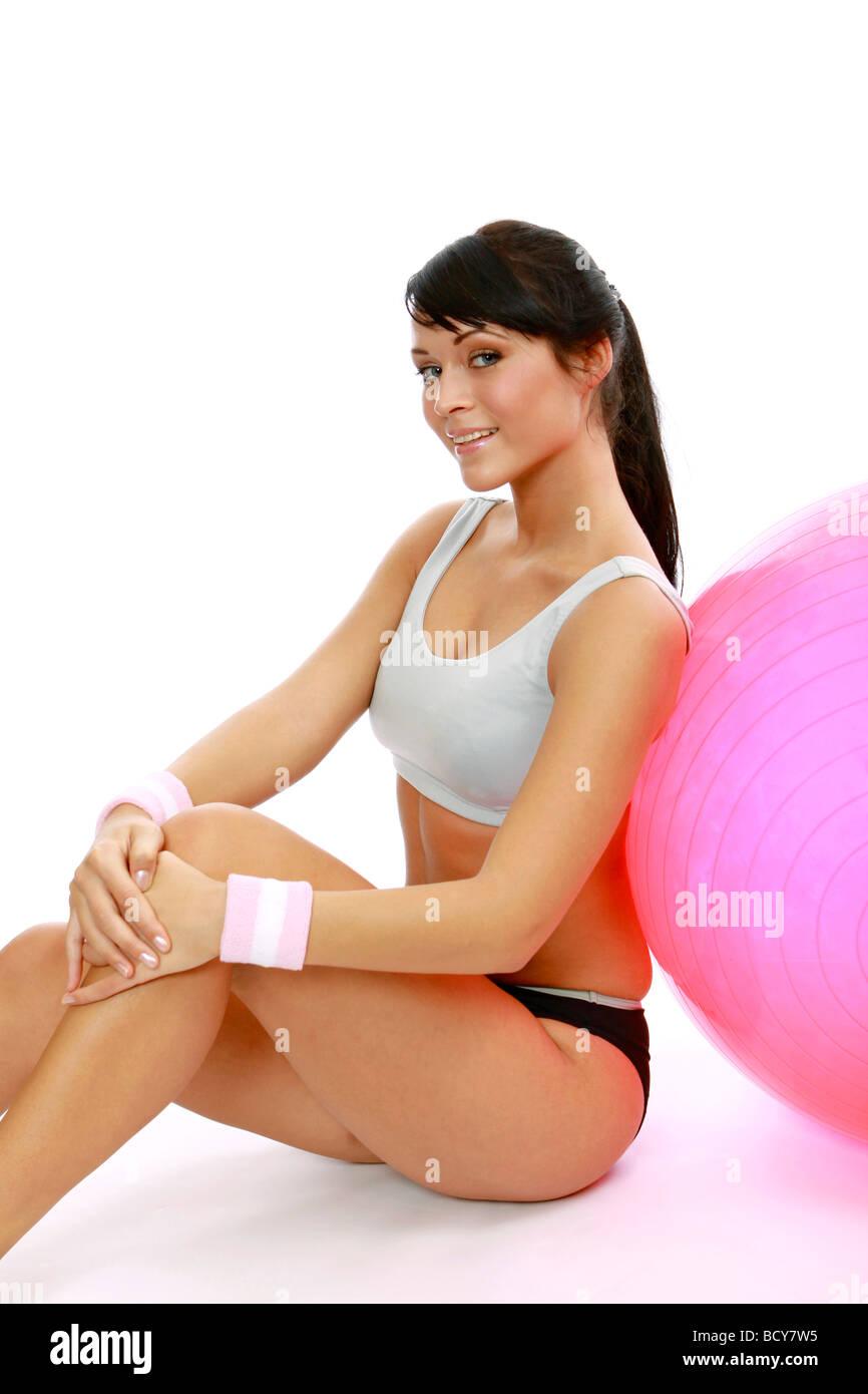 Sportliche Frau macht Pausa auf einem Gymnastikball mujer deportiva hace romper en un ejercicio de pelota Imagen De Stock