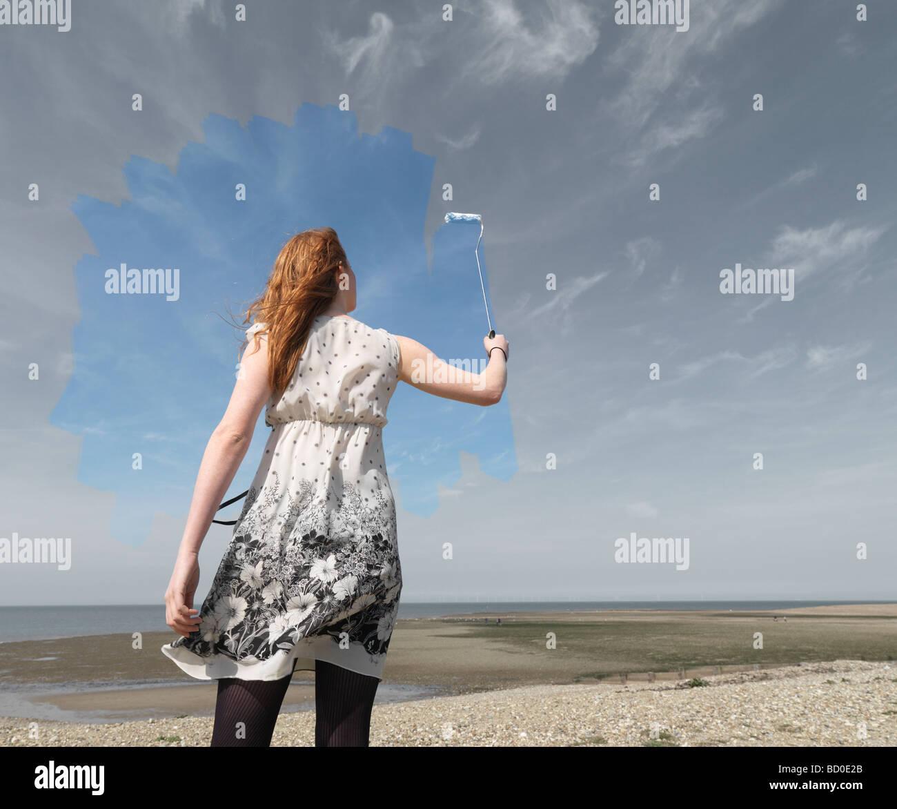 Mujer joven pintura azul cielo gris Imagen De Stock