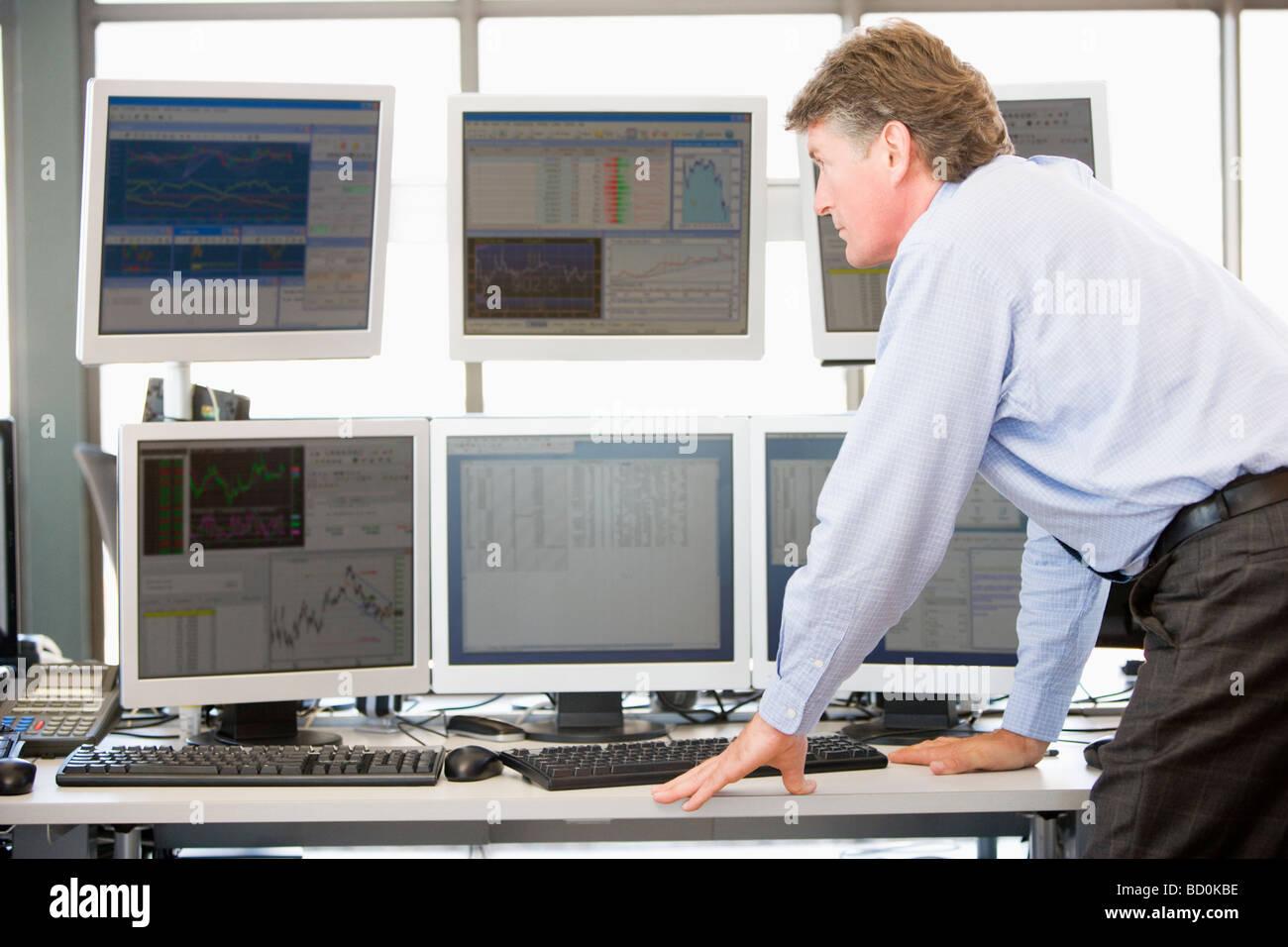 Stock Trader examinando los monitores de ordenador Imagen De Stock