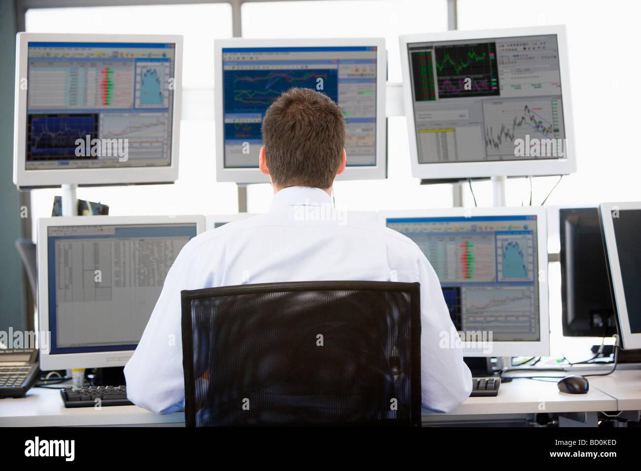 Stock Trader Mirando varios monitores Imagen De Stock