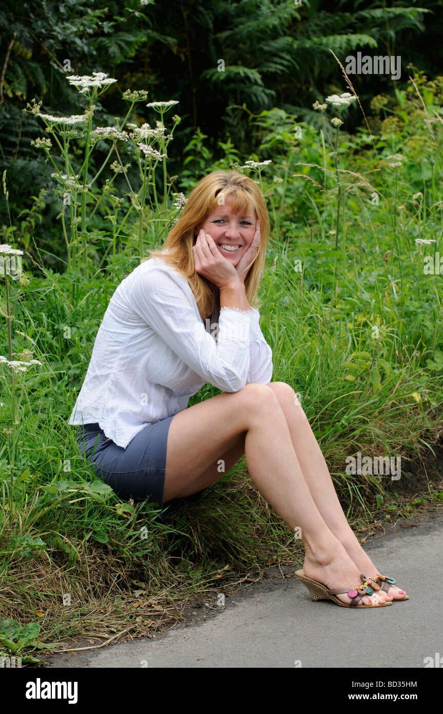 63c4b2065 Mujer madura, llevaba una camisa blanca y una falda sentado al lado ...