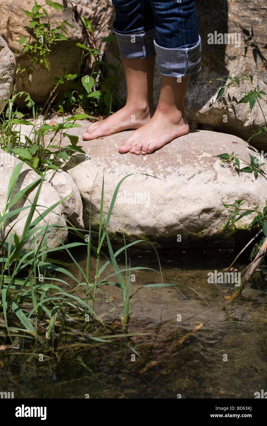 Mujer de pie descalzo sobre las rocas por el río Foto de stock