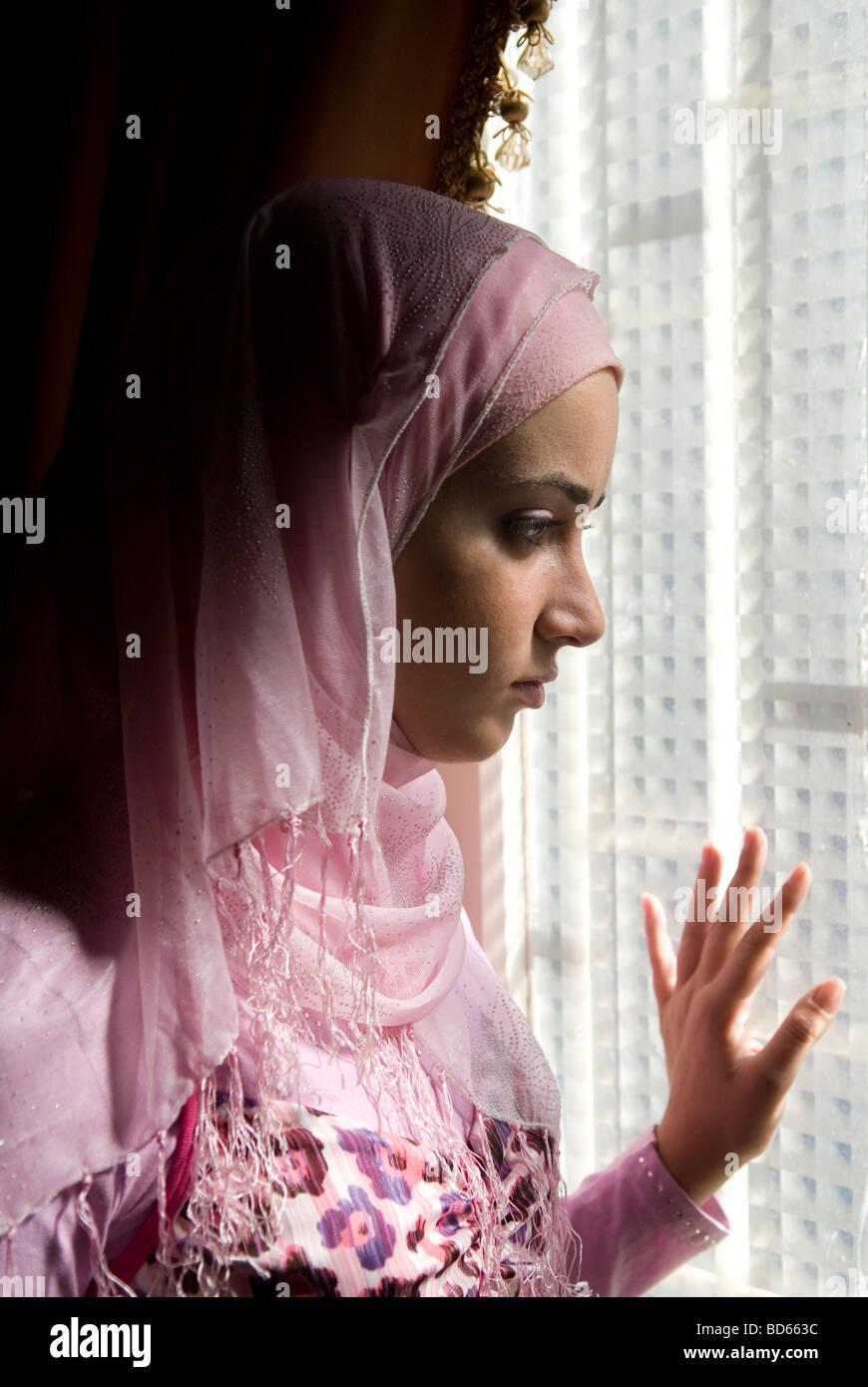Joven chica musulmana mirando por la ventana Imagen De Stock