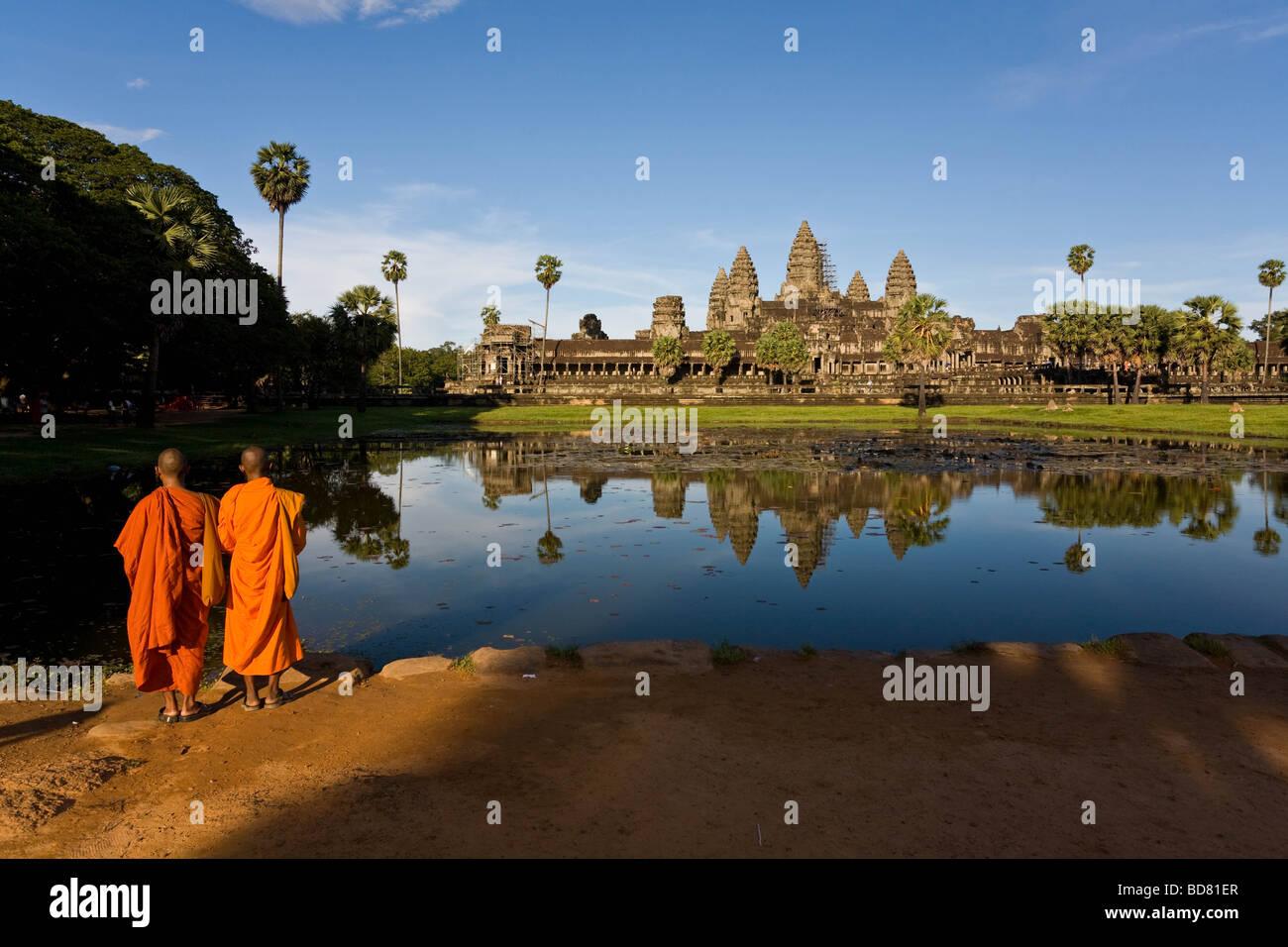 Vista clásica de Angkor Wat a través de las piscinas con un reflejo claro, con dos monjes túnicas Imagen De Stock