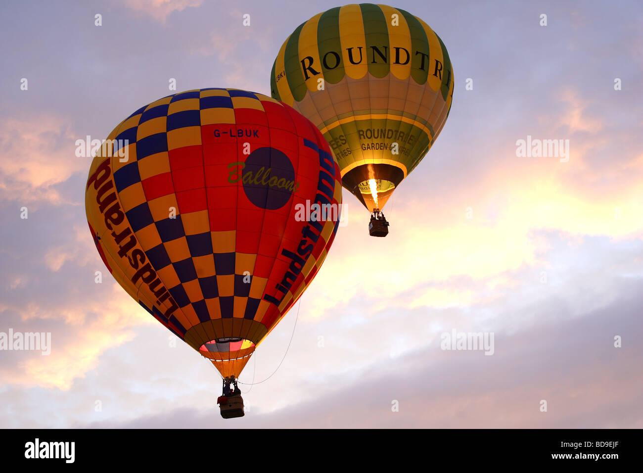 Bristol la fiesta del globo de aire caliente por la mañana temprano el despegue con dos globos Foto de stock
