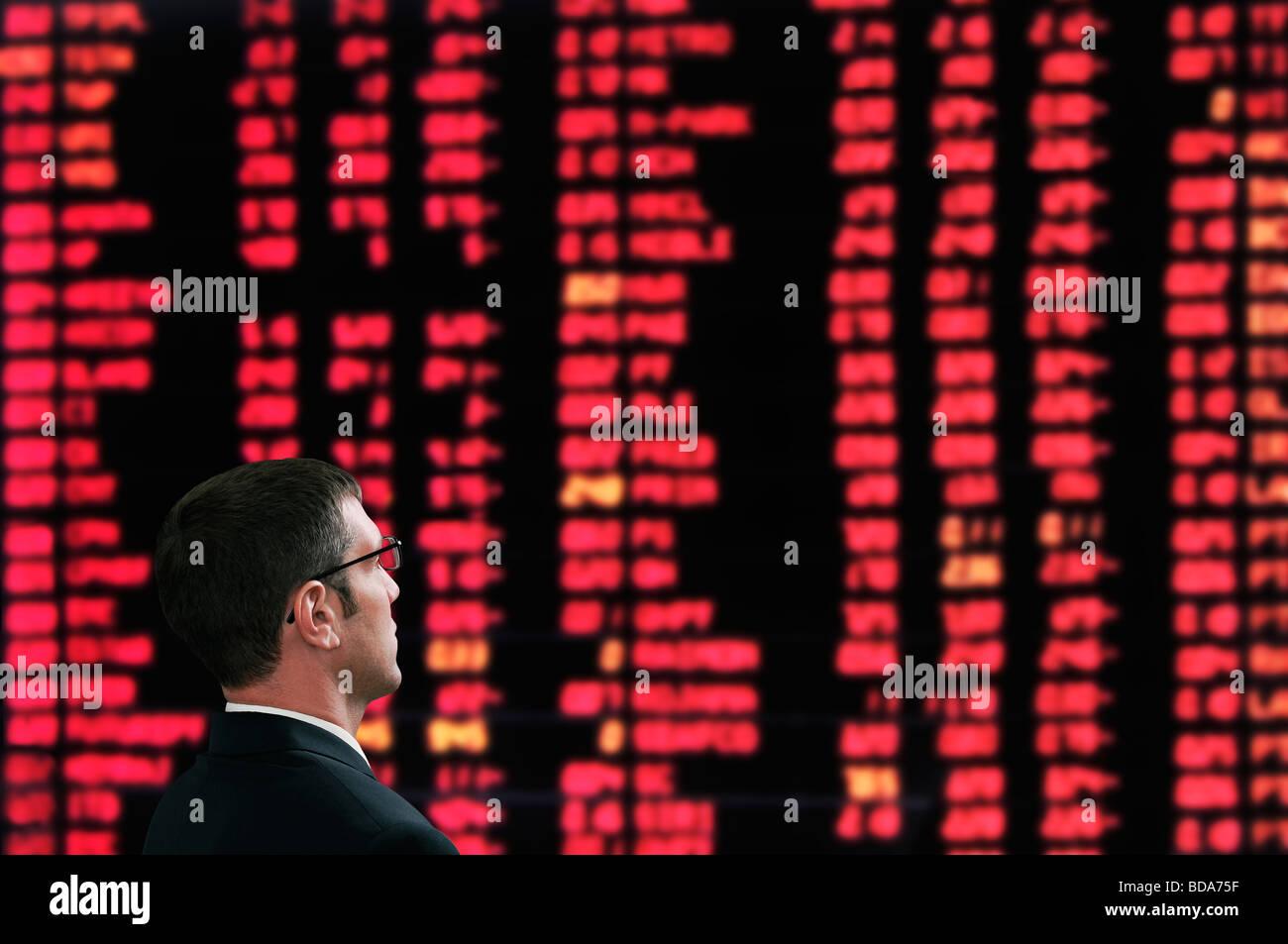 Corredor de bolsa en frente de una pantalla que muestra los precios de mercado en una bolsa de valores Foto de stock