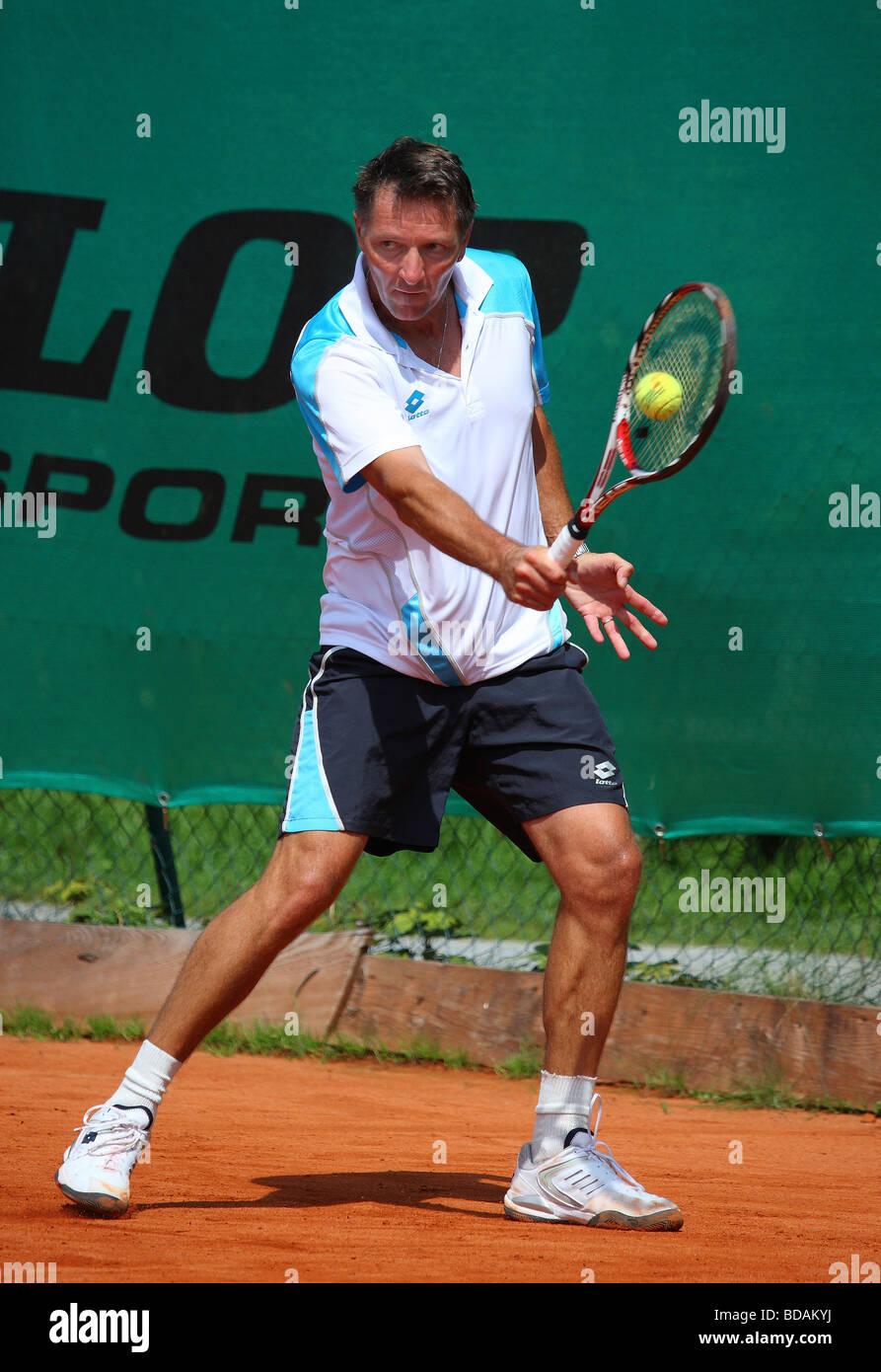 Hombre Middleaged jugando un escrito en un torneo de tenis Imagen De Stock