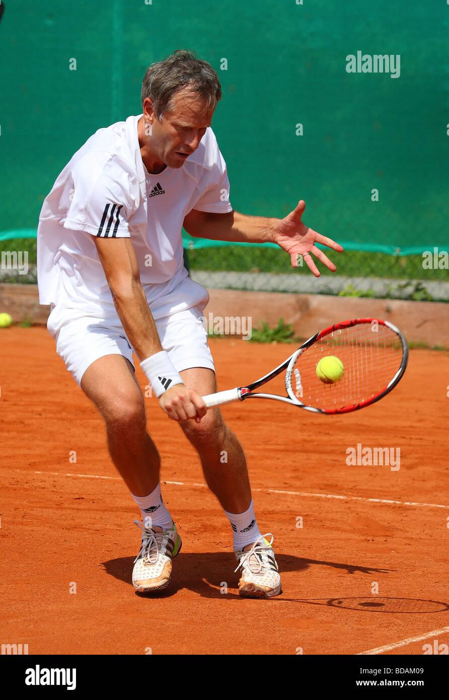 Anciano jugando un escrito en un torneo de tenis Imagen De Stock