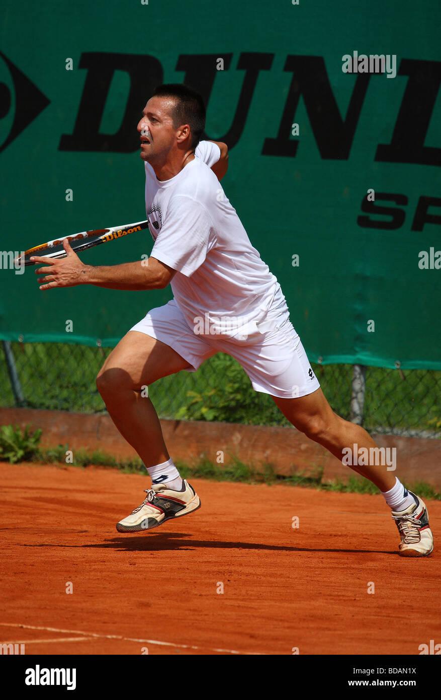 Middleaged,man jugando un escrito en un torneo de tenis Imagen De Stock
