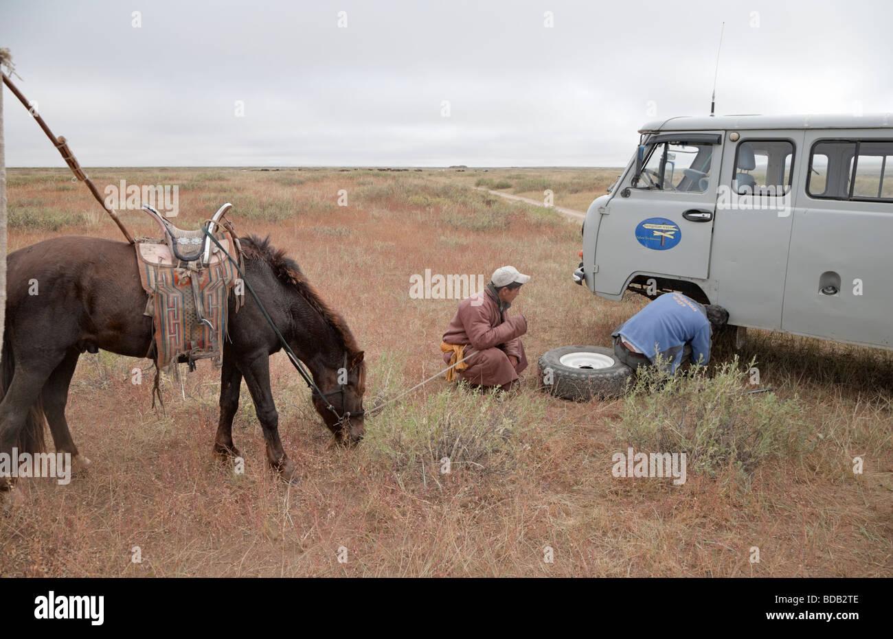 Contrastando los medios de transporte: un jinete mongol supervisa las reparaciones del vehículo, al norte de Mongolia central. Lo que es más fiable? Foto de stock