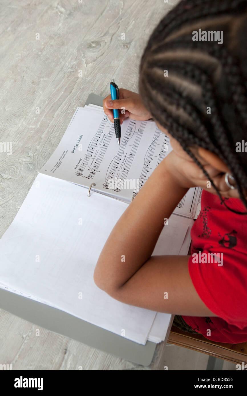 Little Girl está haciendo su tarea de música Imagen De Stock