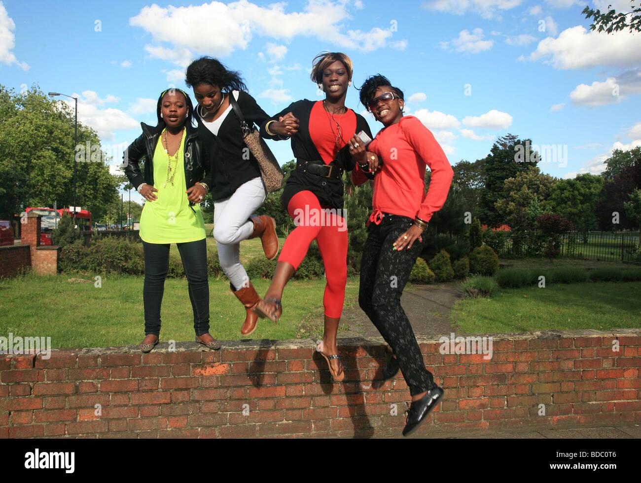 4 elegante negro amigos saltando juntos, London, South, Camberwell UK 2009 Foto de stock