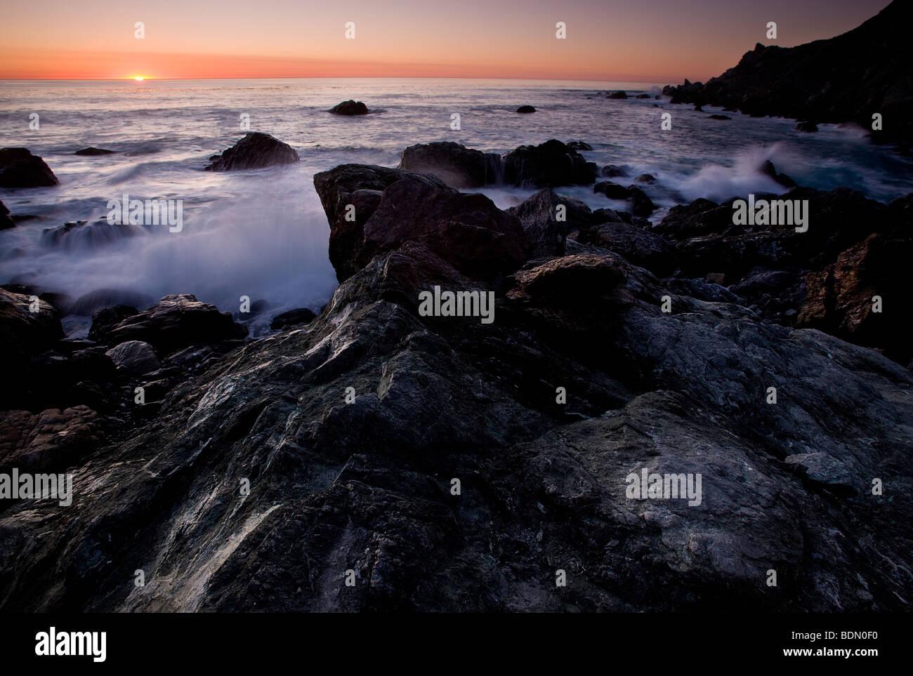 Puesta de sol y rocas negras, Big Sur, California, Estados Unidos. Imagen De Stock