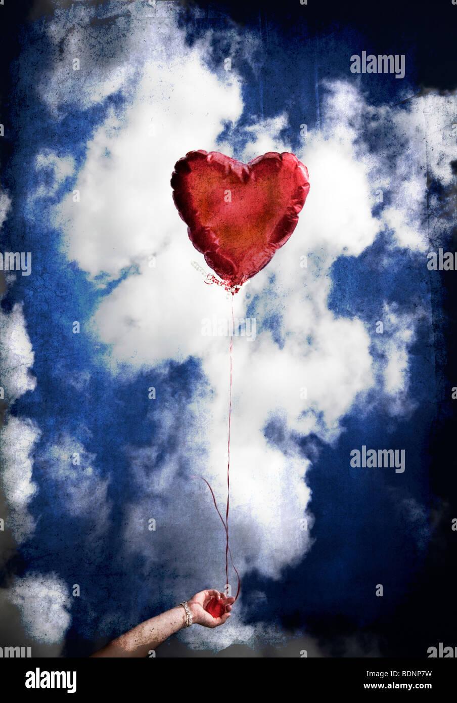 Una niña sostiene un globo rojo con forma de corazón le gustaba contra el cielo azul. Imagen De Stock