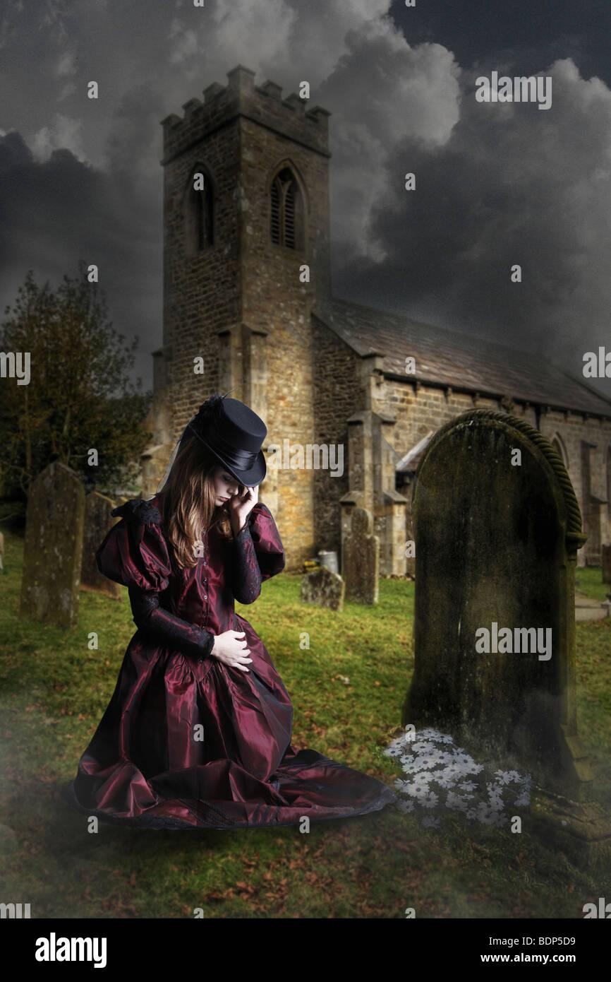 Niña en un cementerio de rodillas por un grave Imagen De Stock
