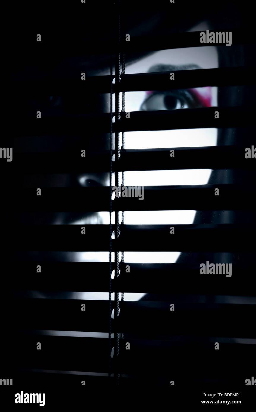 Una cara oculta parcialmente de una joven mujer detrás de una pantalla Foto de stock