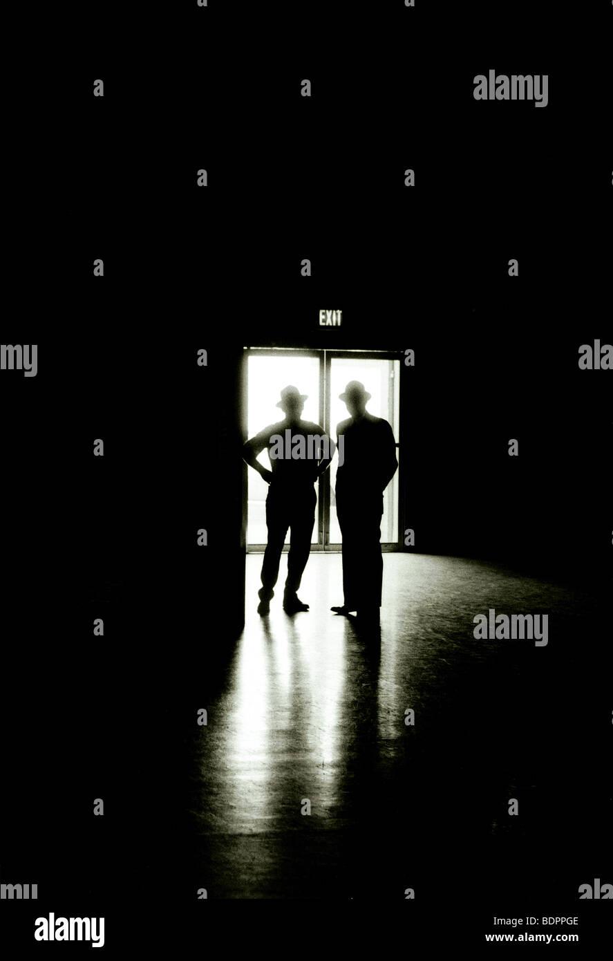 Dos figuras masculinas siluetas contra una puerta de salida Imagen De Stock