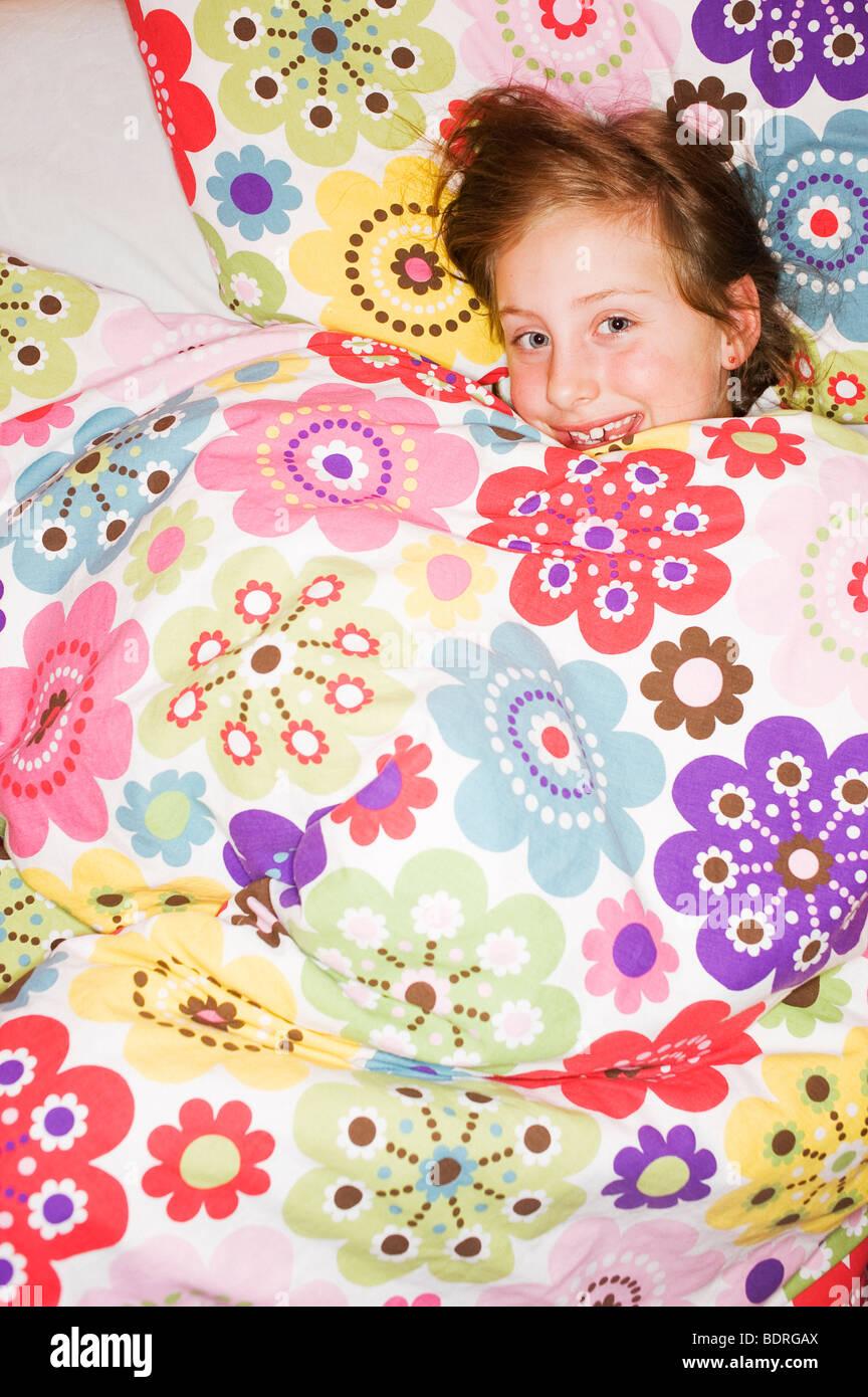 Una niña alegre que yacía bajo un edredón florido Imagen De Stock