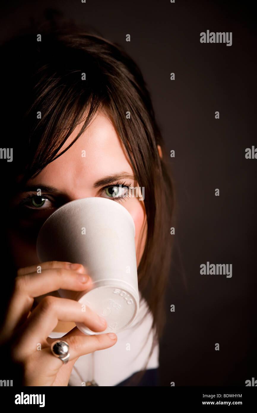 """Hermosa joven """"ocultar"""" detrás de una taza de poliestireno. Foto de stock"""