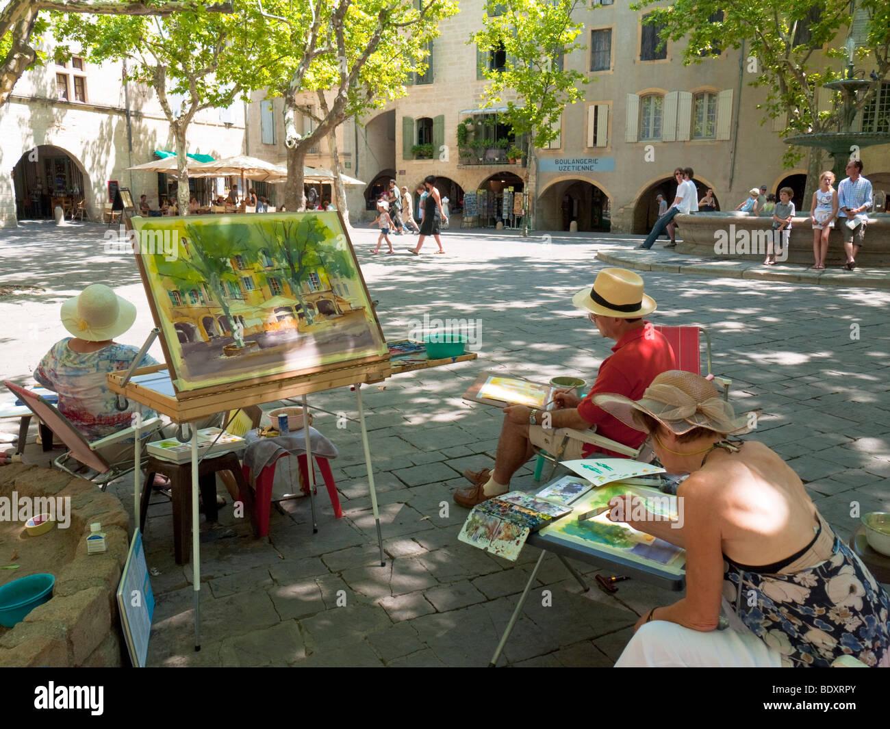 Hobby pintores trabajan en la plaza central Place aux Herbes en Uzès, en el sur de Francia. Imagen De Stock