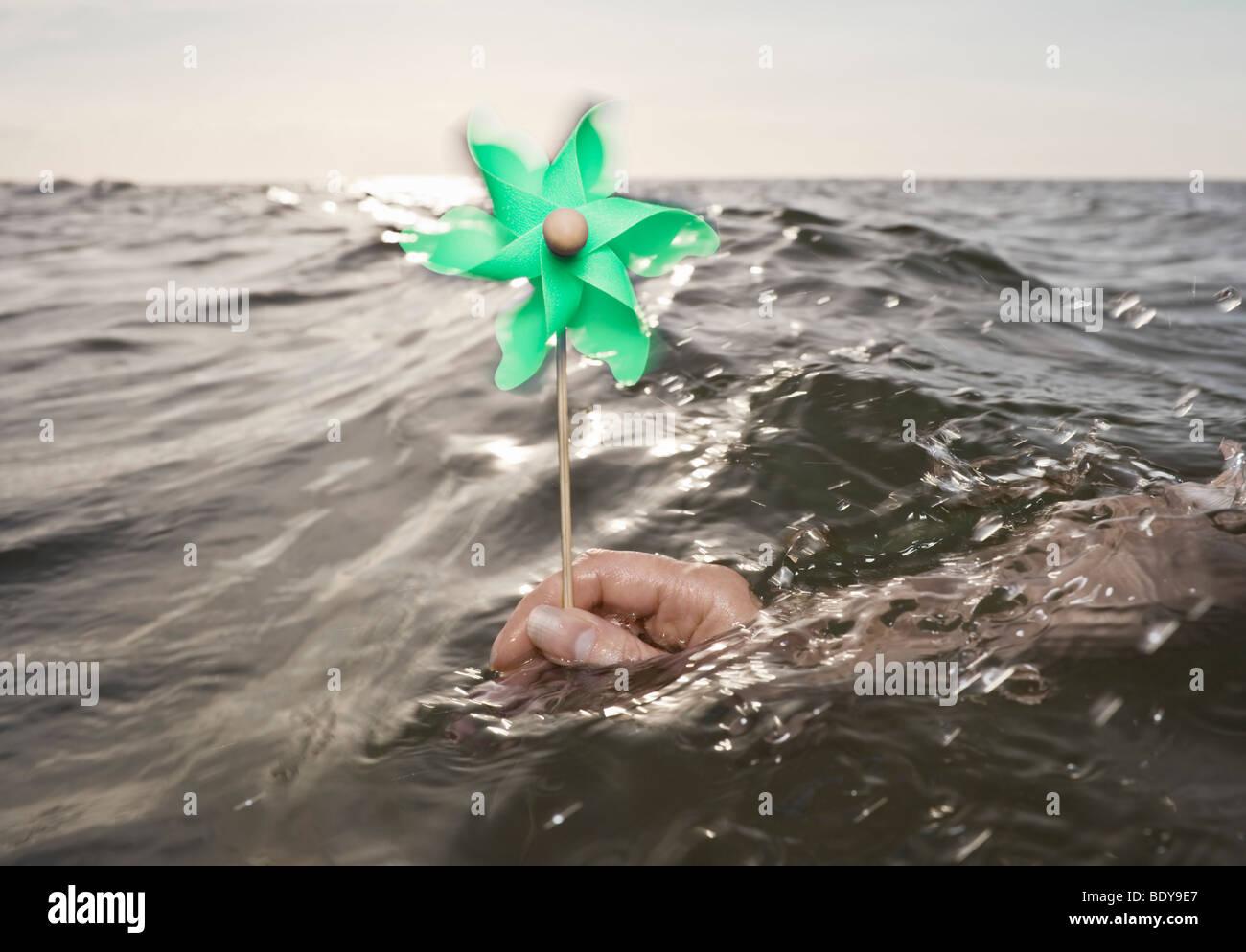 Brazo sujetando el molino de viento hacia el mar Imagen De Stock