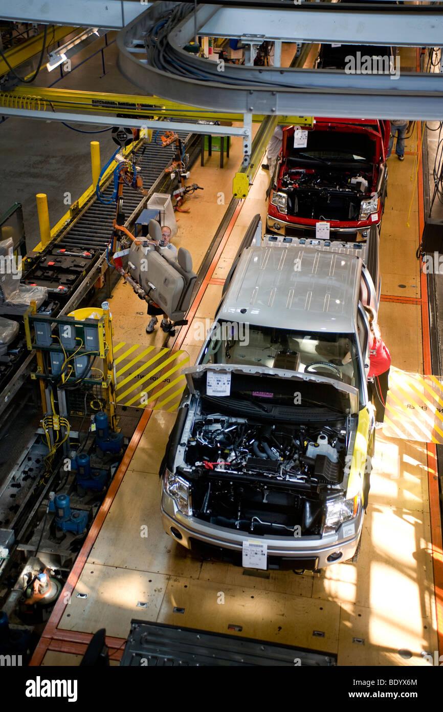 Un trabajador de una fábrica de material de tapicería interior lleva a una camionetas F-150 de Ford en Imagen De Stock
