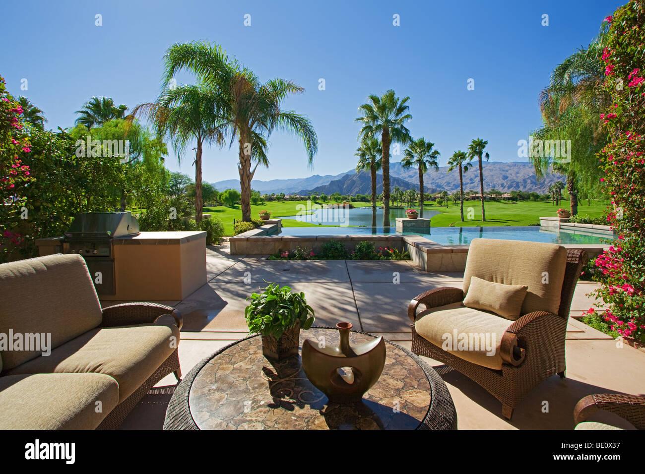 Vista diurna de asientos al aire libre con piscina en segundo plano. Imagen De Stock