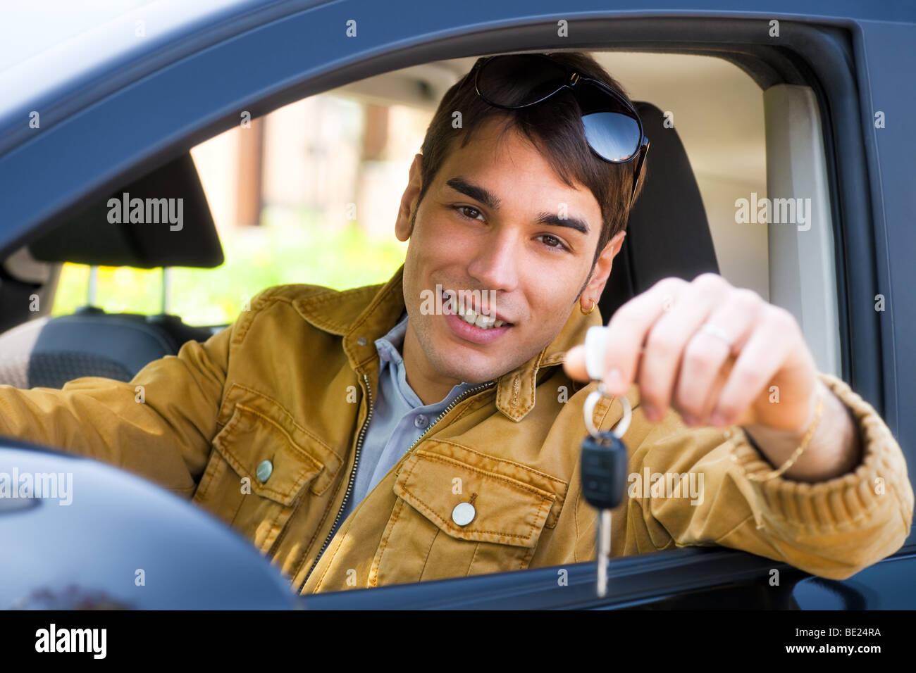Hombre joven sentado dentro del vehículo mostrando claves para coche Nuevo Imagen De Stock