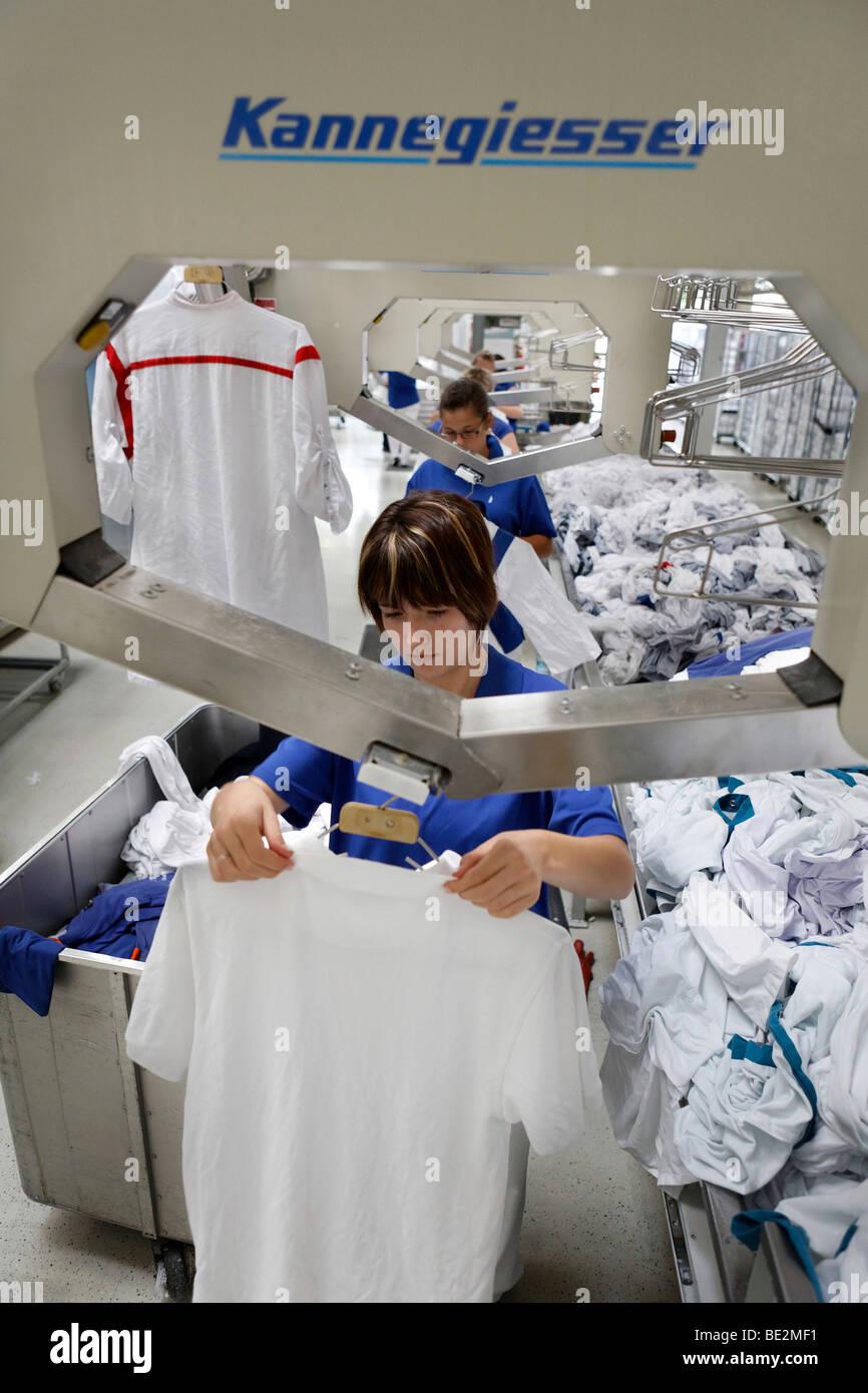 Sabina Uhrig colgando recién lavados y todavía la ropa húmeda en coathangers delante de la Hotbox Imagen De Stock