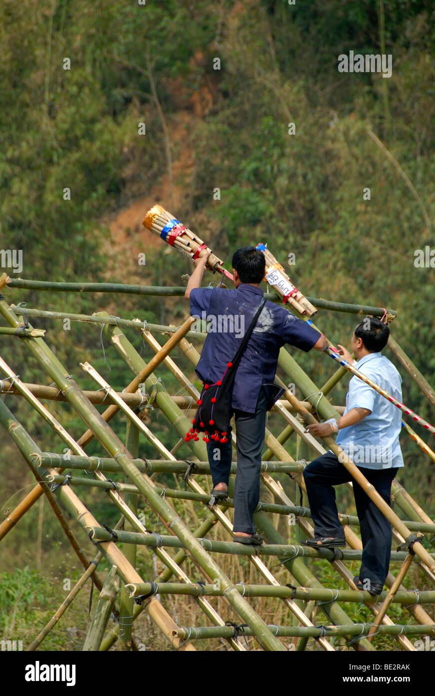 Hombres colocando los fuegos artificiales en una plataforma de lanzamiento, Pi Mai Lao, la fiesta de Año Nuevo, Imagen De Stock
