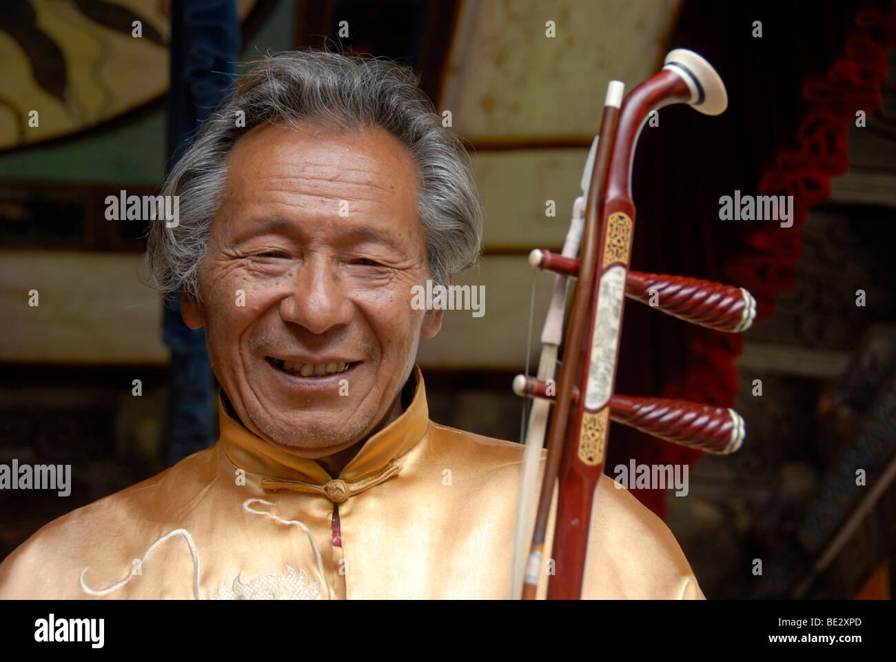 Retrato, músico, Nakhi Naxi sonriente, el hombre con el instrumento de cuerda, Lijiang, Sitio del Patrimonio Mundial de la UNESCO, en la provincia de Yunnan, Peopl Foto de stock