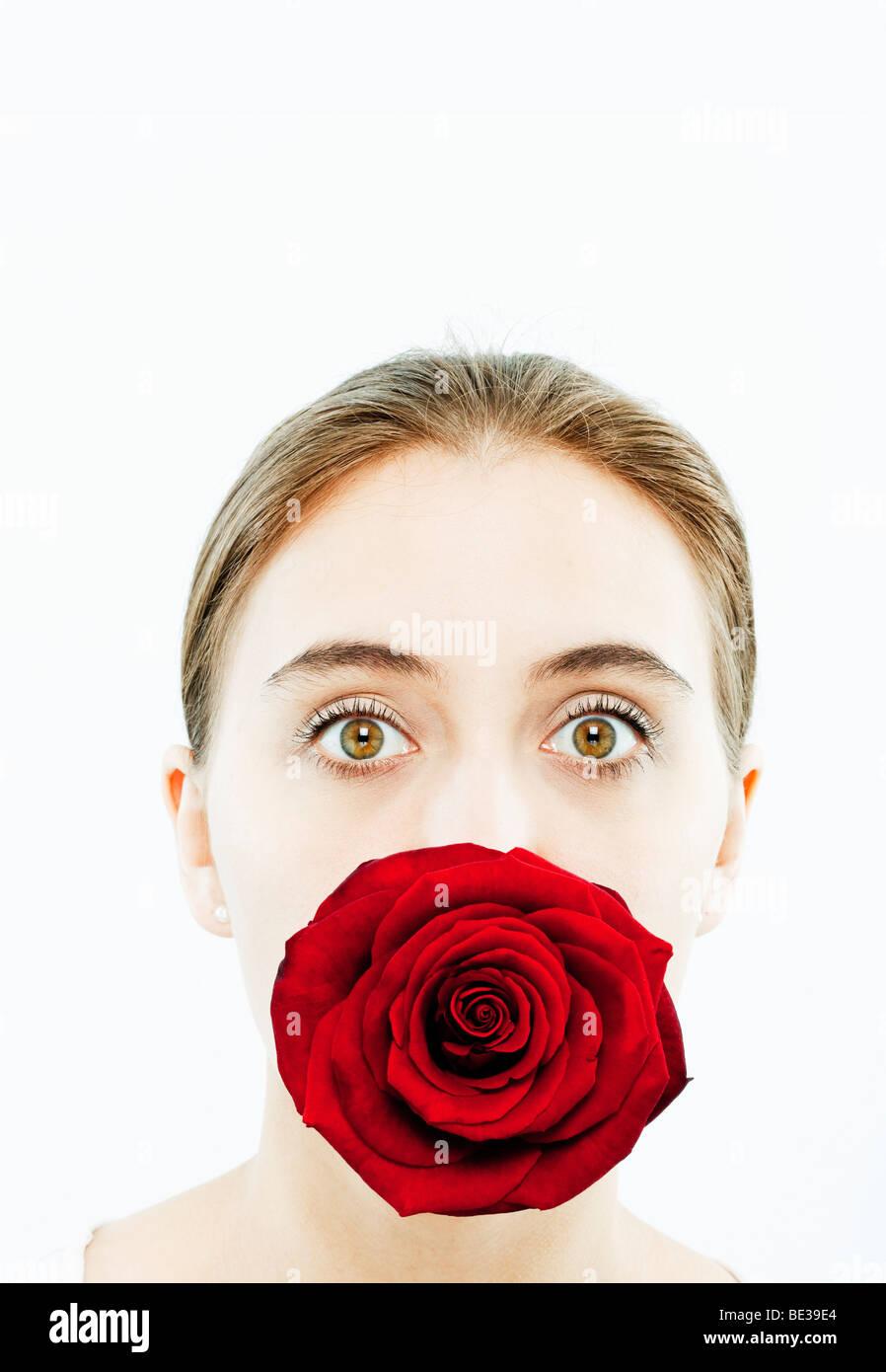 Retrato de mujer joven con una rosa en su boca Imagen De Stock