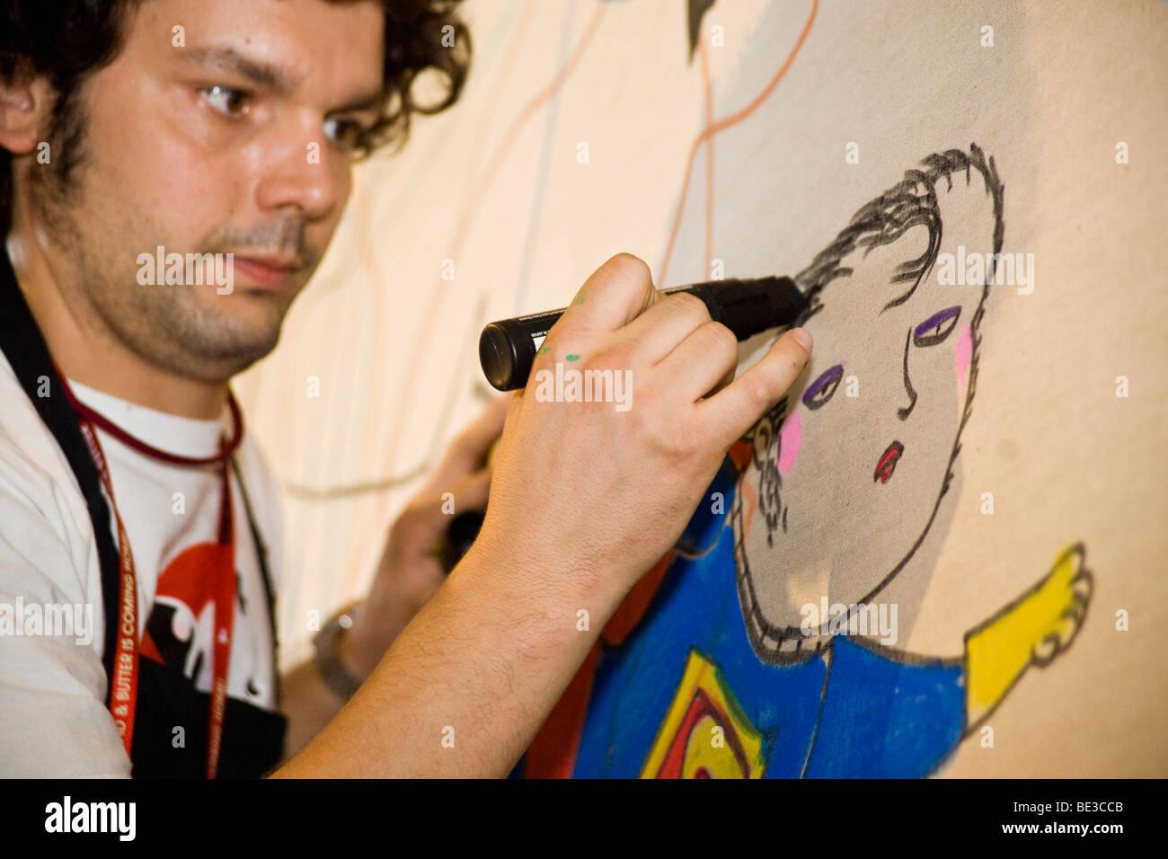 El pintor valenciano Vicente Ramirez está dibujando una nueva imagen cada día en la feria de moda Bread Imagen De Stock