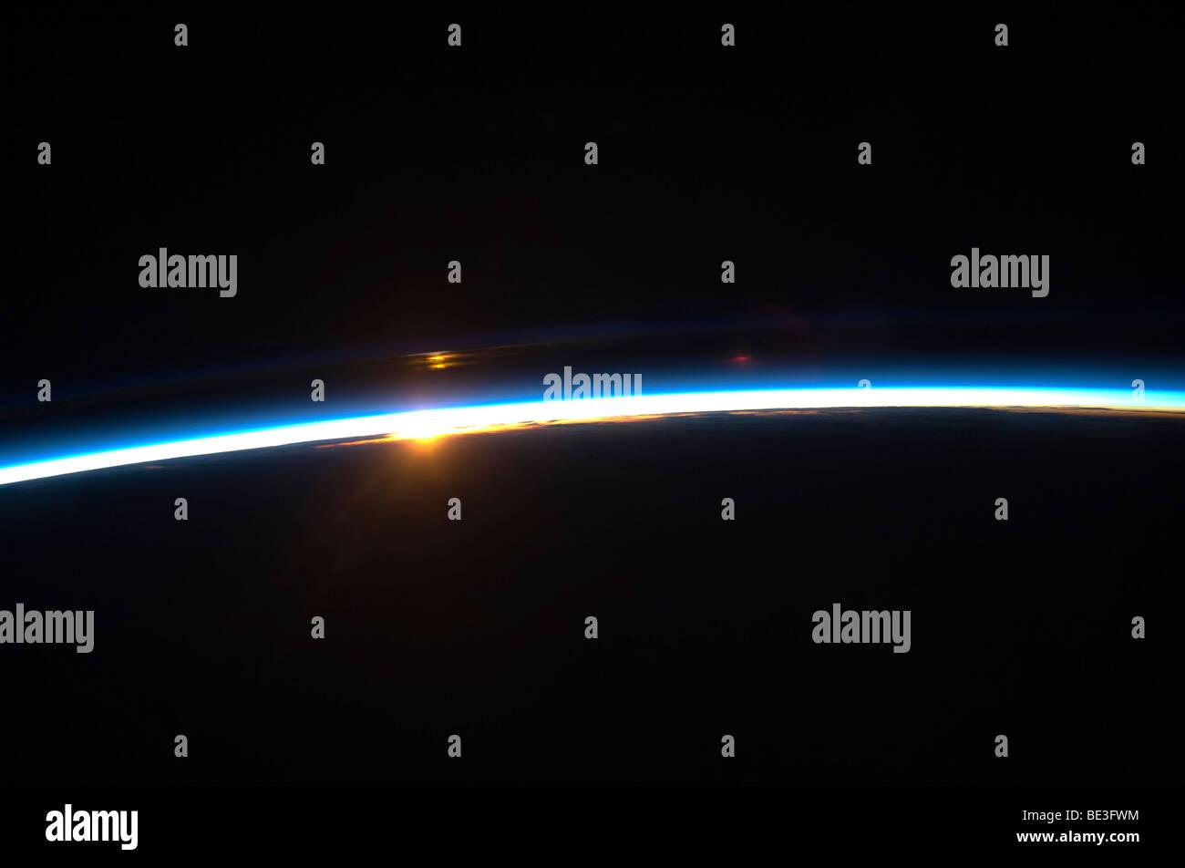 La delgada línea de la atmósfera de la tierra y el sol naciente. Imagen De Stock