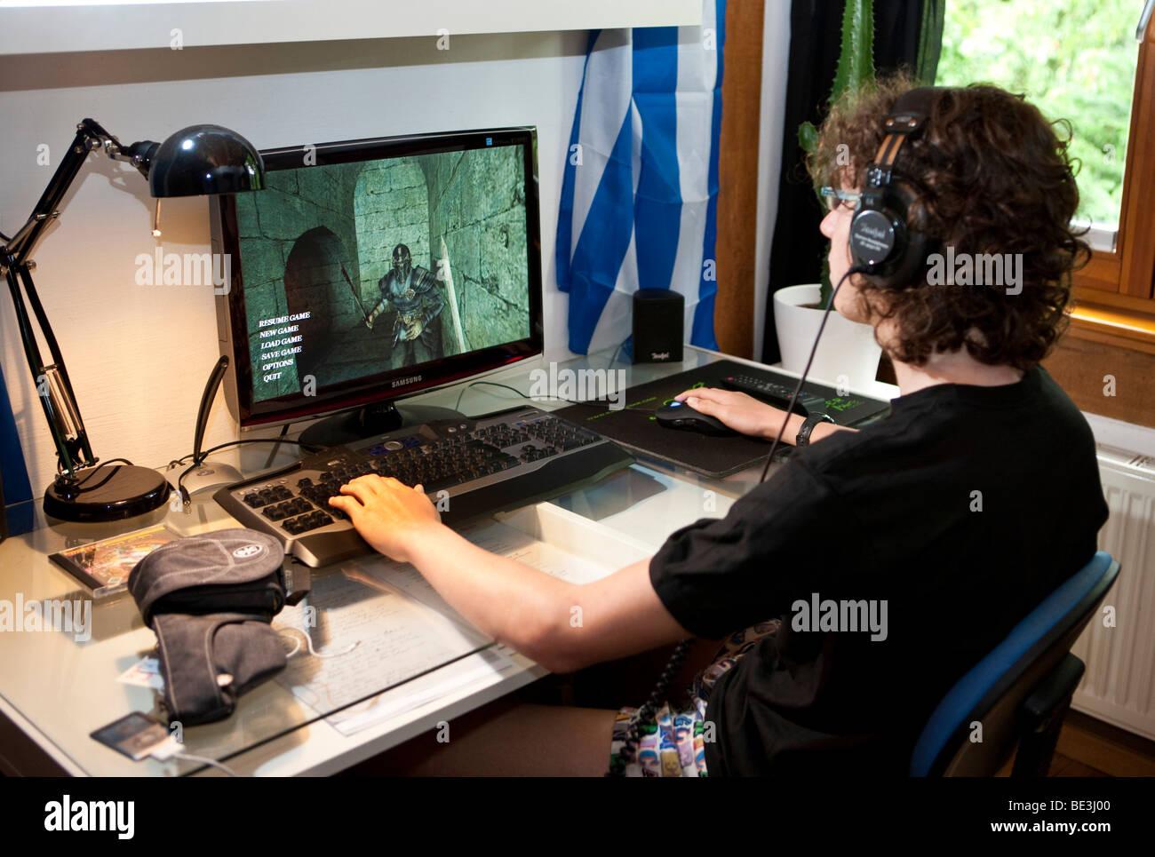 Un muchacho, de unos 15 años, jugando a un juego violento en el ordenador en su habitación, Alemania, Imagen De Stock