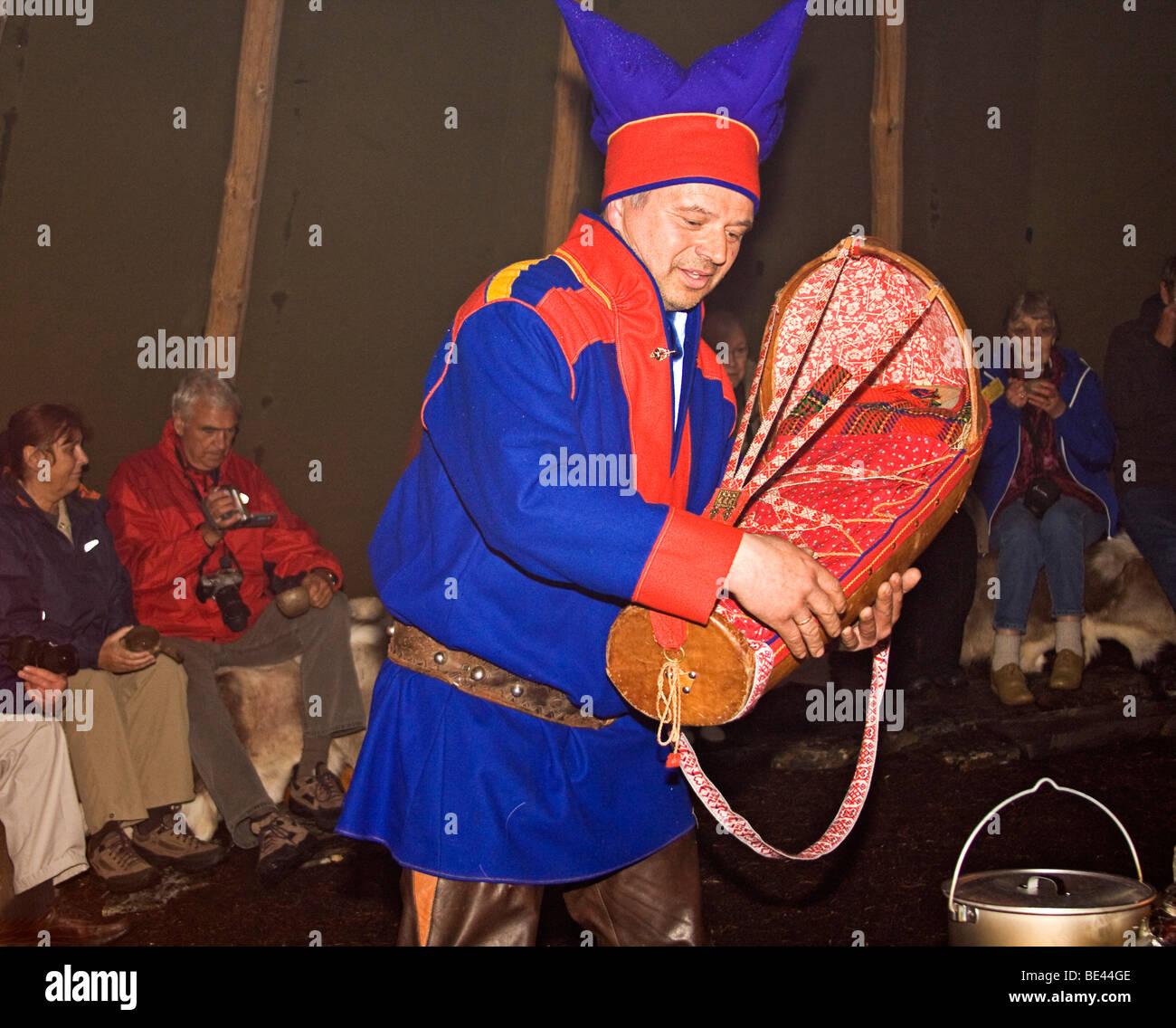 Hombre Sami en vestimentas tradicionales muestra una cuna utilizada para los bebés y las conversaciones acerca Imagen De Stock