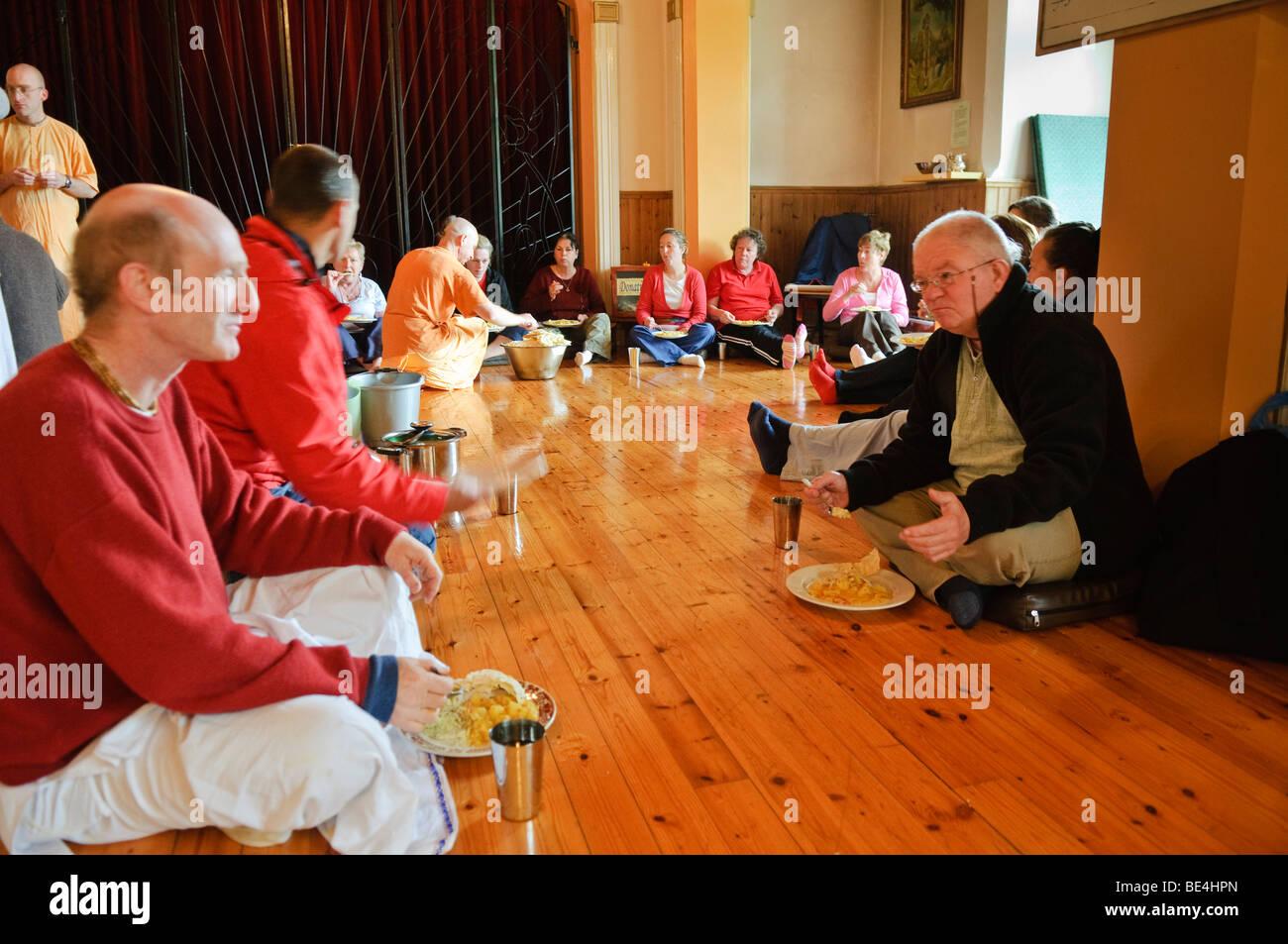Hare Krishna ISKCON discípulos y visitantes comer vegetariano fiesta en una habitación del templo Foto de stock