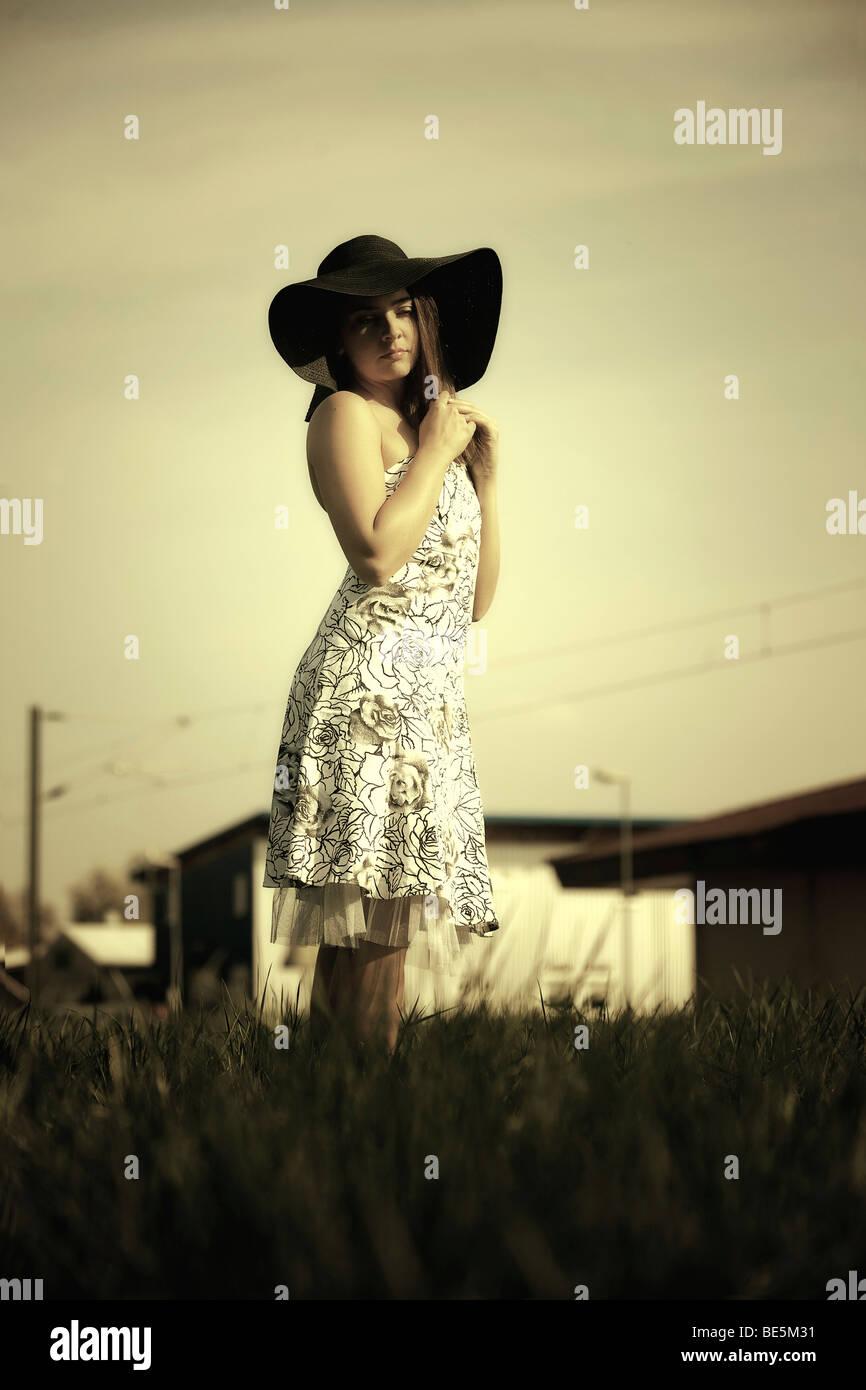 Mujer joven con un vestido de verano florido y gran sombrero está de pie en una pradera y mirar el sol Imagen De Stock