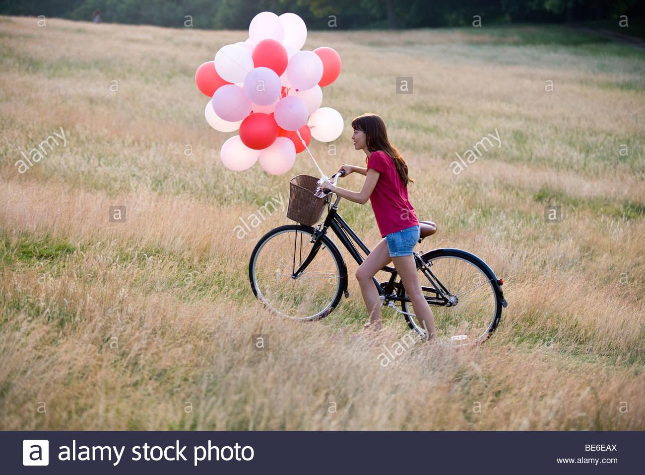 Una joven mujer sosteniendo un montón de globos, empujando una bicicleta Imagen De Stock
