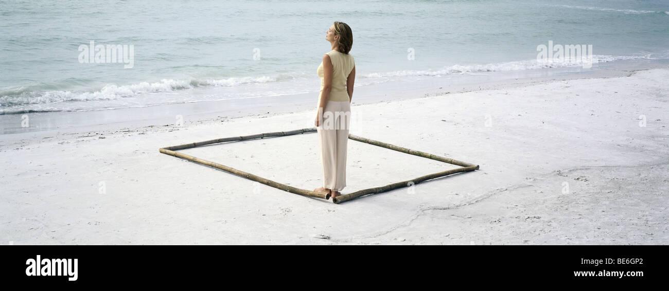 Mujer de pie en la esquina de la plaza esbozado en playa por longitudes de bambú Imagen De Stock