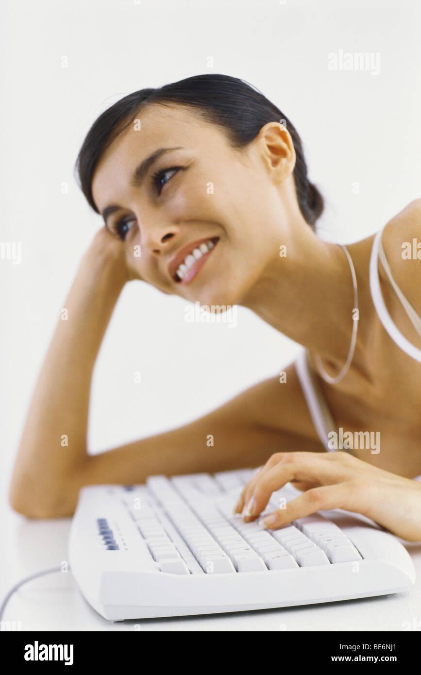 Mujer recostada sobre el codo escribiendo en el teclado, sonriendo Foto de stock