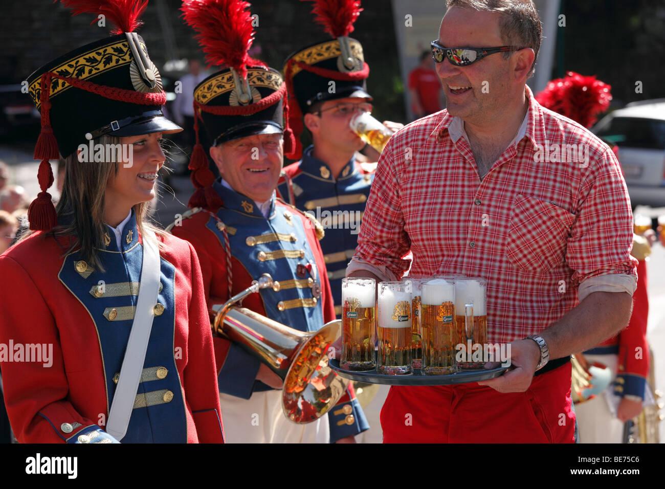 Dueño servir cerveza para el grupo de música local de San Miguel, en el Desfile de Sansón, Katschberg, Lungau, estado Foto de stock